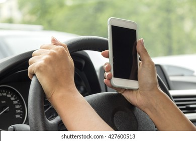 girl with a mobile phone behind the wheel in the saloon car
