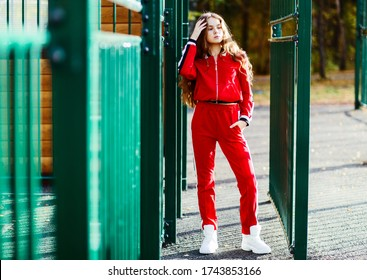 a girl model 14 years old stands next to the green fence at the entrance to the court in a red tracksuit with long curly hair brown hair in the bright sun in white sneakers posing demonstrating clothe