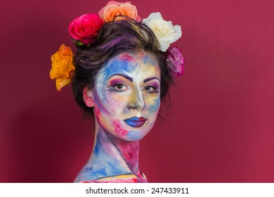 Girl model beauty-fashion photography. Bright, colorful make-up. Flowers, roses in her hair. Beautiful girl with make-up of creative work. Floral make-up.