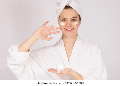 Girl model with face cream and towel on her head, concept of skin ageing care and skin products, on white background with copy space