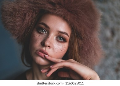 Girl model. girl in a fluffy hat with ear-flaps. studio portrait. Face in freckles. Winter fashion. gentle look. makeup. Stylish Look. hairdressing procedures. professional styling. manicure.