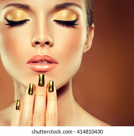 Girl model with  Golden makeup and gold  metal manicure  nails. Cosmetics,makeup and beauty