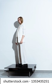 Girl model on the background of a white wall in a white pantsuit. Fashion shooting.