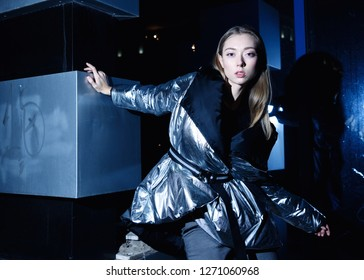 girl model in silver down jacket, on the street at night.