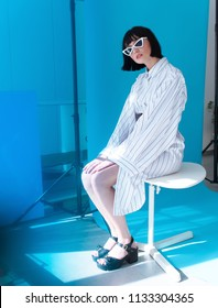 girl model in white dress and glasses, blue background in studio, fashion photography.