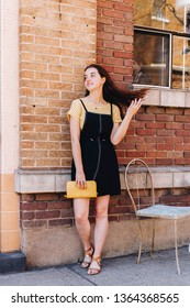 Girl modeling cute casual summer outfit outdoors against brick wall playing with her hair wearing a yellow striped shirt, black dress, and sandals. Holding a yellow clutch/wallet.