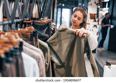Girl is in modern store with new clothes. Elegant expensive wear.