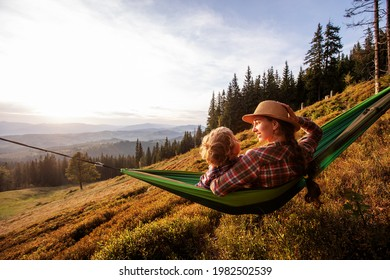 Girl with mom resting in a hammock in the mountains - Shutterstock ID 1982502539