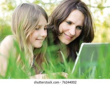 Girl and mommy working on notebook computer outdoor