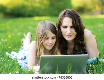 Girl and mommy working on notebook computer
