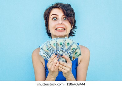 Girl with money on blue background. Happy funny young woman holding dollars