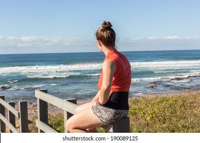 Girl Morning Beach Ocean Young teen girl on beach coastline walkway steps sits watching morning ocean waves with playtime fun to relax.