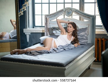 The girl in the morning in the bedroom on silk bed linen, in white shorts and a T-shirt