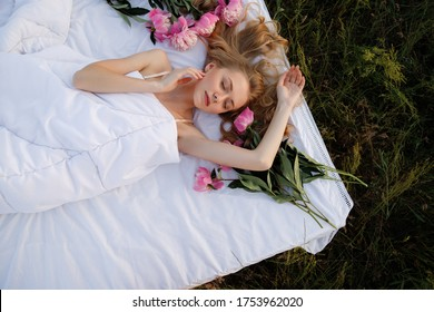 girl in the morning in the field sits on a white bed with a glass of wine and a bouquet of peonies. summer photo shoot