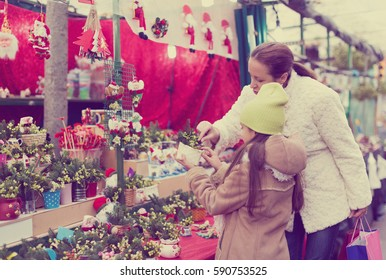 girl with mother choosing mistletoe decorations for Christmas. Focus on woman