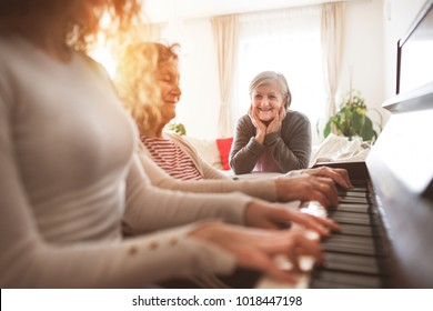 A girl with mother and grandmother playing the piano.