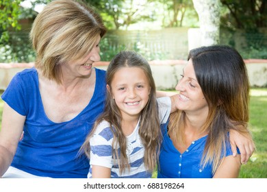 girl with mother and the grandmother walks on the park, smile and pose on the camera, relations between the senior and younger generation, close-knit family