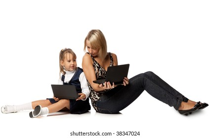 The girl and mother sit a back to each other with laptops on a white background.