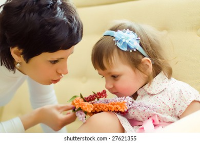 girl with mother sniffing flowers