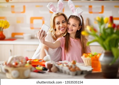 Girl with mother taking selfie with cell phone while painting Easter eggs