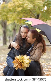 Girl with mother under umbrella. yellow leaves at autumn