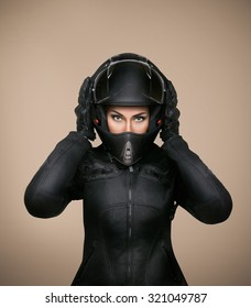 Girl motorcyclist in a black jacket, helmet and gloves