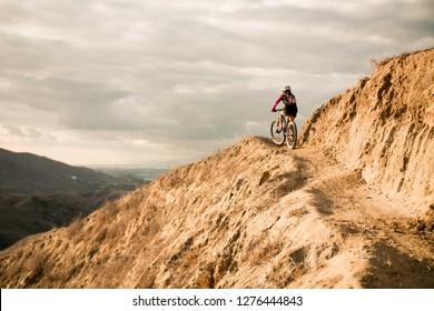 Girl mountain biking in the hills