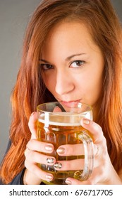 girl with a mug of light beer. an alcoholic drink made from yeast-fermented malt flavored with hops.
