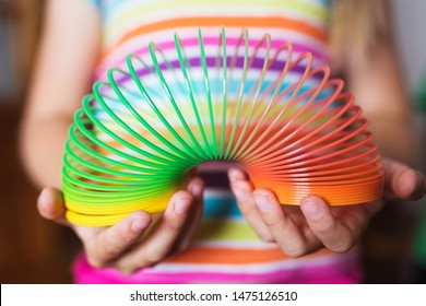 A girl in a multi-colored T-shirt holds a multi-colored slinky toy in her hands - focus on her hands