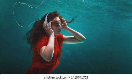 Girl music fan enjoys the music, the concept. Deep dive. Young brunette woman with headphones on her head and underwater