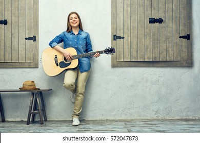 Girl musician with acoustic guitar full body portrait.