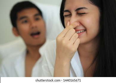 The girl must close her nose because she can not tolerate her of the husband mouth odor.