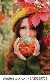 Girl in mustard yellow knit hat and marsh green wool sweater cover her mouth with a small orange pumpkin among colorful ivy in autumn
