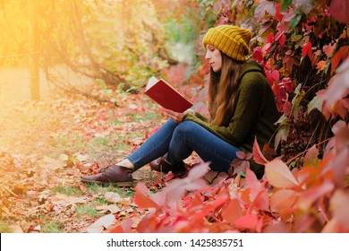 Girl in mustard yellow knit hat and marsh green wool sweater sitting among colorful ivy in autumn and reading a paper book.