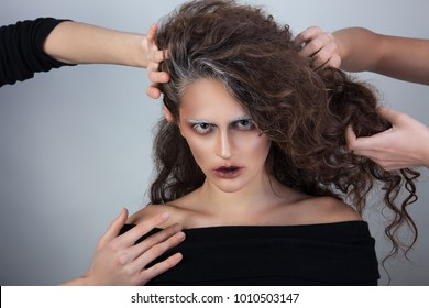 a girl in a mysterious image who holds her hands by her hair and throat