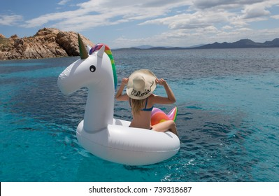 Girl named Viktoria is sitting on inflatable unicorn float in Emerald Coast of Sardinia.