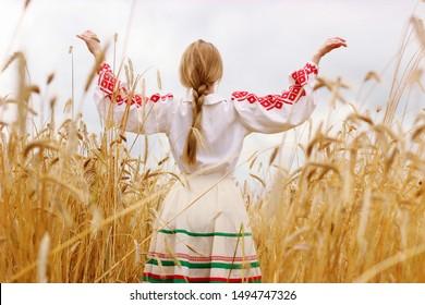 Girl in national Belarusian costume on a golden wheat field