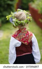 Girl in national costume wearing flower wreath, Sandhamn, Sweden