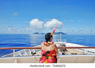 Girl in national Tonga dress is watching the sea in front of the ship