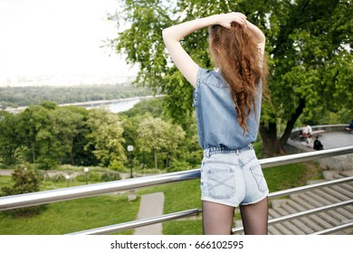 Girl in navy blue jeans shirt and shorts is holding her hair in hands