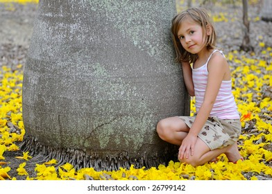 Girl near the big tree surrounded by yellow flowers