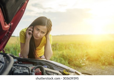 Girl near a broken car on the country road is calling on mobile phone.