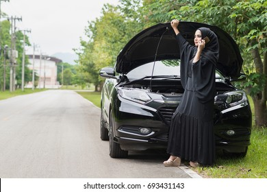Girl near a broken car on the road is calling on mobile phone.