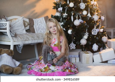 The girl near a Christmas tree with a favorite toy rabbit, boxes, Christmas, New Year, lifestyle, holiday, vacation, waiting for santa