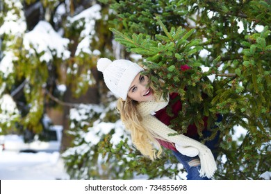 girl near a Christmas tree in the street in a forest in a red jacket and a knitted white hat snow is happy nature in winter a positive photo of a snowfall