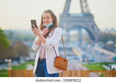 Girl near Eiffel tower in Paris with half-removed face mask during coronavirus outbreak, taking selfie or recording video blog. Pandemic and lockdown in France. Tourist spending vacation in France