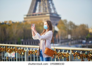 Girl near Eiffel tower in Paris wearing mask and taking selfie or recording video blog during coronavirus outbreak. Pandemic and lockdown in France. Tourist spending vacation in France during pandemic