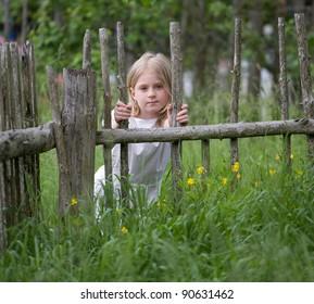 The girl, near a fence has hidden