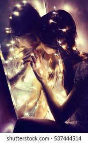 Girl near the mirror.  She entwined with lights and touches the looking-glass