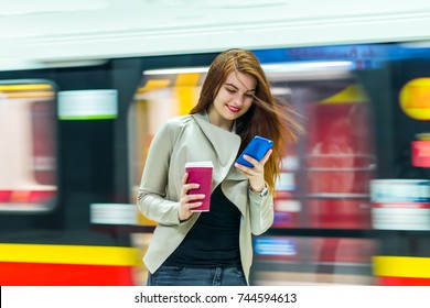 The girl near subway train and looking at the smartphone at the metro station